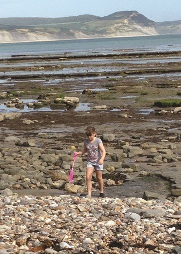 Deaf child on the beach with a spade