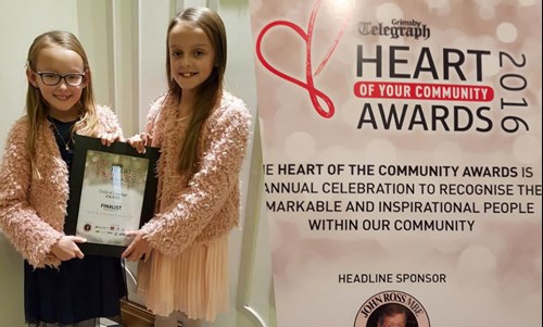 Deaf child and twin sister win award