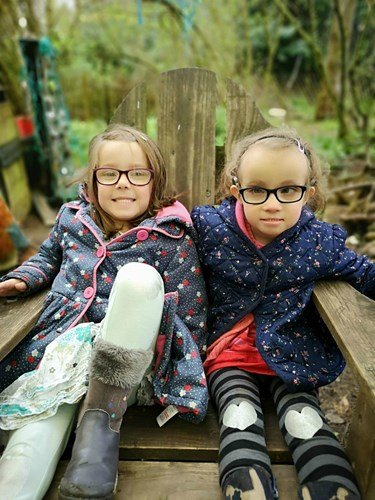 Matilda and Olivia sitting on a bench outdoors