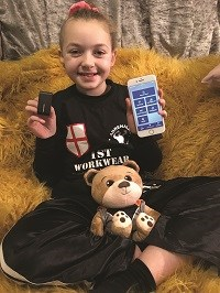 Poppy holding up her phone and the Oticon Medical Ponto 4 and ConnectClip.