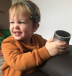 Charlie laughs while holding the Damson wireless speaker. He wears cochlear implant processors on a softband.